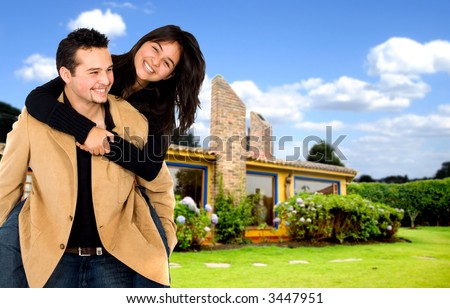 young couple having fun at home with their house in the background - stock photo