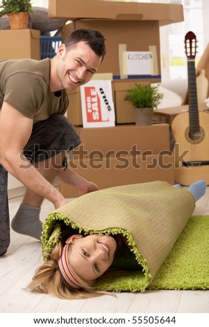 Young couple having fun at moving house, laughing man rolling girlfriend into carpet. - stock photo