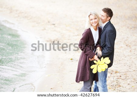 Young couple having fun at the beach. They are happy and smiling. - stock photo