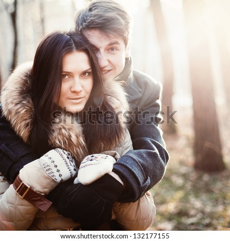 Young couple having fun in park in cold spring - stock photo