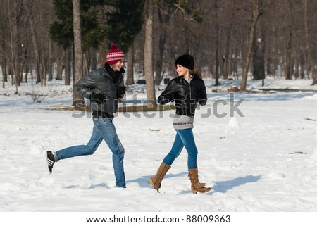 young couple having fun in the park, in winter holidays