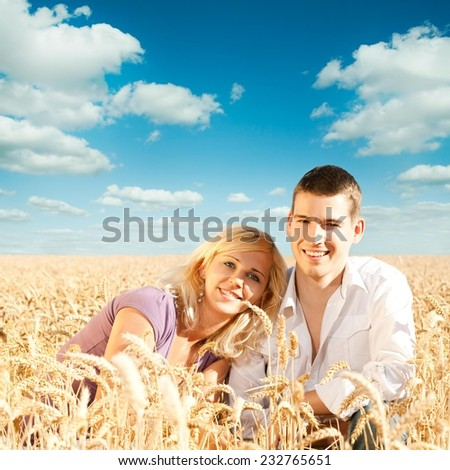 Young couple having fun in the wheat field - stock photo