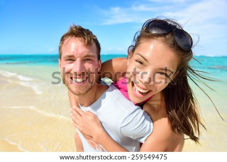 Young couple having fun laughing on beach holidays. Beautiful Asian mixed race woman piggybacking on Caucasian male excited at camera portrait. Multicultural, multiethnic, multiracial people. - stock photo