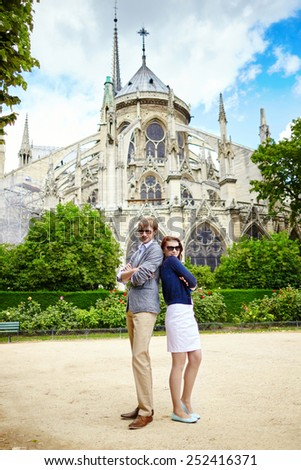 Young couple having fun near Notre-Dame cathedral in Paris - stock photo