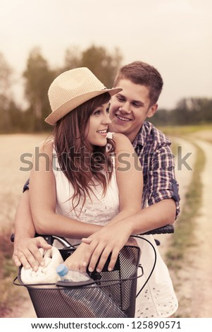 Young couple having fun on bicycle - stock photo