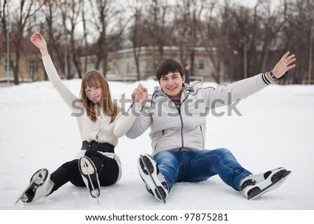 Young couple having fun on ice skate rink outdoors. - stock photo