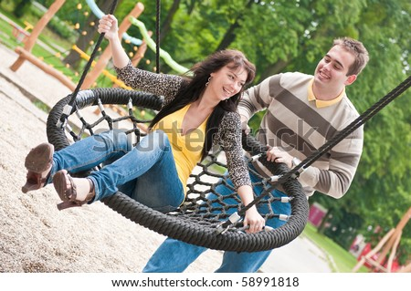 Young couple having fun - outdoors on children playground