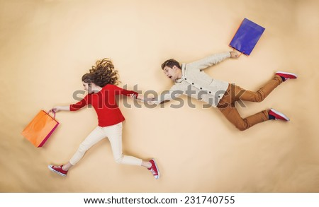 Young couple having fun running with shopping bags against the beige background - stock photo