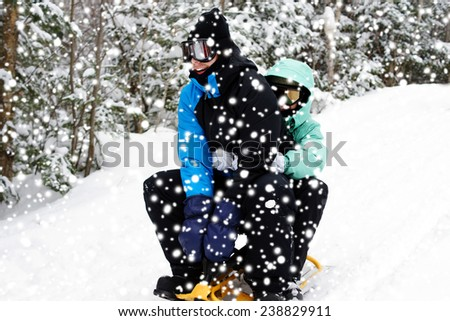 Young couple having fun sliding on the snow, winter sport concept - stock photo