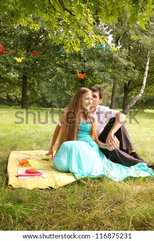 young couple having fun talking at a picnic - stock photo