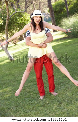 Young Couple Having Fun Together In Garden - stock photo