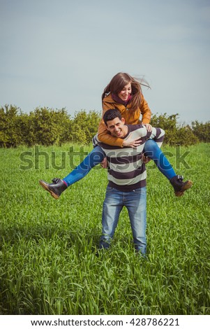 Young couple having fun together in green field. The woman riding piggyback on man shoulders. - stock photo