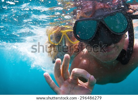 Young couple having fun underwater and showing ok sign - stock photo