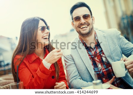Young couple having fun while sitting together in a city cafe. - stock photo