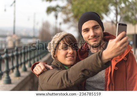 Young couple having fun with mobile photography on the street - stock photo