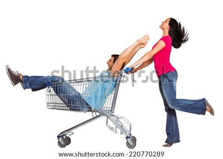 Young couple having fun with shopping cart on white background - stock photo