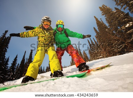Young couple having fun with snowboards at sunset time. - stock photo