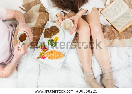 Young couple having healthy breakfast in bed. Light snacks. the beginning of a new day. top view - stock photo