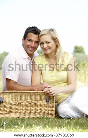 Young couple having picnic in countryside - stock photo
