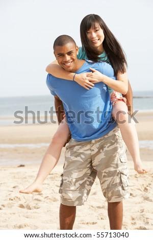 Young Couple Having Piggyback Fun On Beach - stock photo