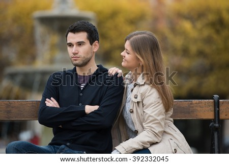 young couple having romantic conversation after love fight on the bench in park in Paris, France - stock photo