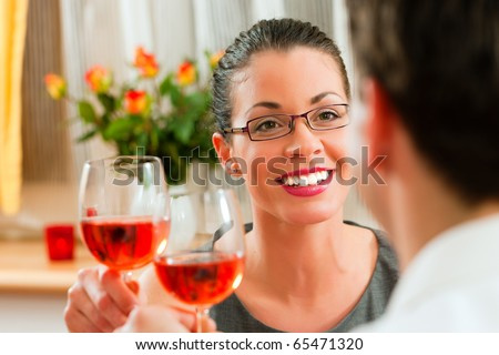 Young couple having romantic dinner - both drinking rose wine - stock photo
