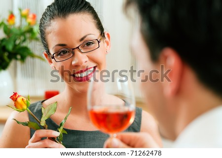 Young couple having romantic dinner � he is drinking rose wine - stock photo