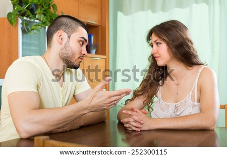 Young couple having serious talking in home interior