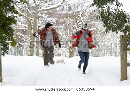 Young couple having snowball fight - stock photo