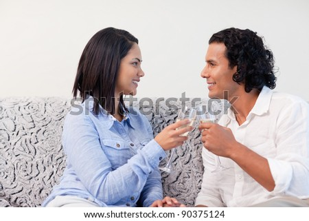 Young couple having sparkling wine on the sofa