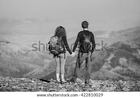 Young couple hikers with backpacks standing on the ridge of the mountain, enjoying the view of beautiful open overlook on the mountains. Couple is holding hands. black and white - stock photo