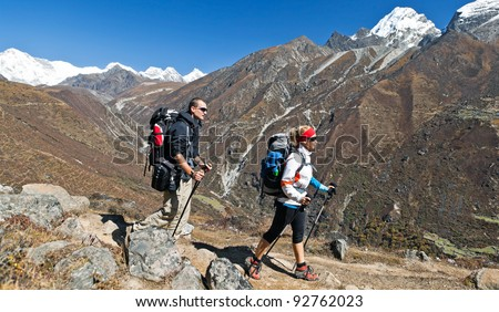 Young couple hiking in himalayas mountains in Nepal. Young people traveling in Asia, trekkers on trail in wilderness. - stock photo