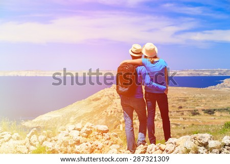 young couple hiking in mountains looking at scenic view, travel concept - stock photo