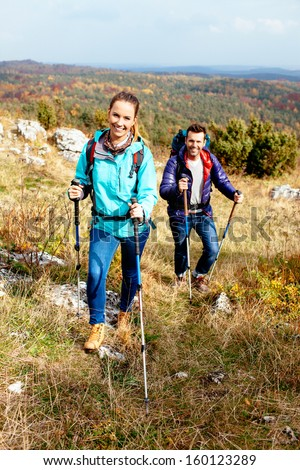 Young couple hiking in nature with sticks. Nordic walking - stock photo