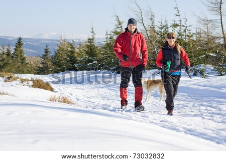 Young couple hiking in winter mountains. Young people traveling in Poland. Man and woman trekkers on snow trail in forest.