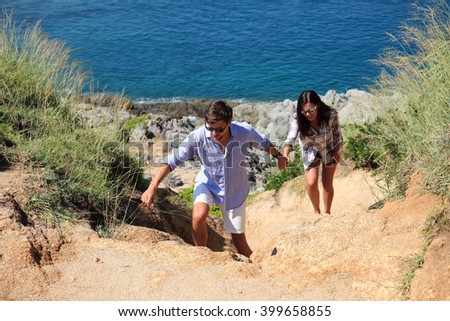 Young couple hiking on the hill near sea - stock photo
