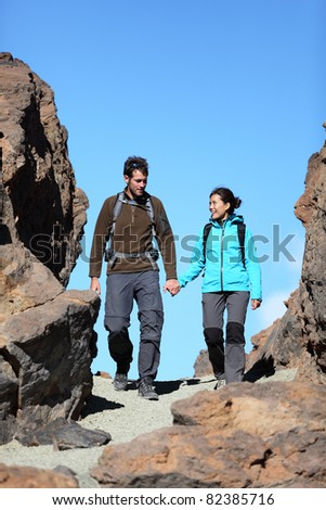 Young couple hiking outdoors holding hands talking during hike trip in beautiful volcano landscape on Teide, Tenerife, Canary Islands. - stock photo