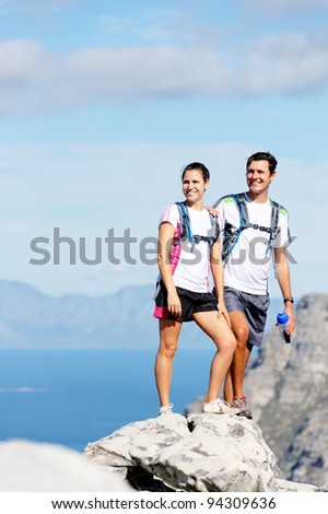 young couple hiking outdoors in the sunshine, healthy lifestyle concept - stock photo