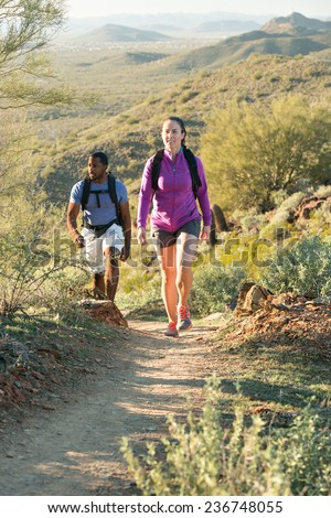 Young couple hiking outdoors on a trail at Phoenix Sonoran Preserve in Phoenix, Arizona.