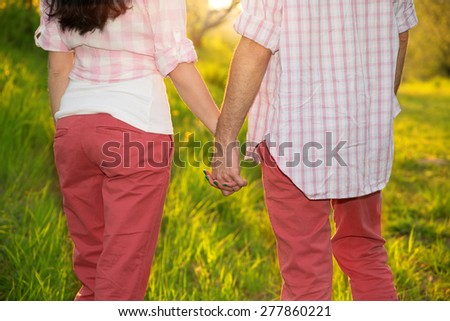 Young couple hold each other's hands summer on sunny park background. Concept shoot of friendship and love of man and woman. Two hands over sun ray and nature. Young couple in Love Story on nature.