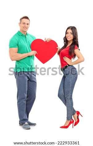 Young couple holding a big red heart isolated on white background