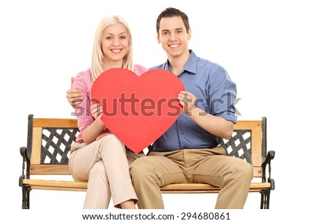 Young couple holding a big red heart seated on a wooden bench and looking at the camera isolated on white background - stock photo