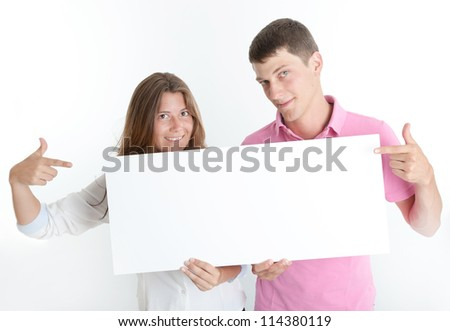 Young couple holding a blank board, ideal for inserting your own message - stock photo