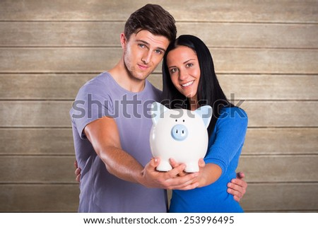Young couple holding a piggy bank against wooden surface with planks - stock photo