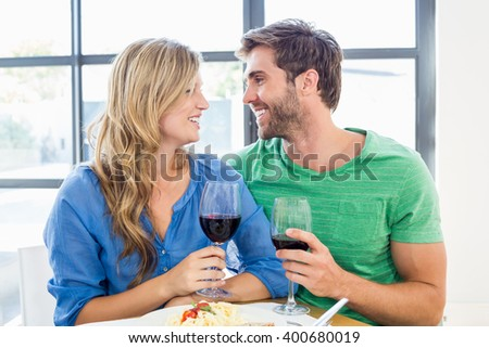 Young couple holding a wine glass at home - stock photo
