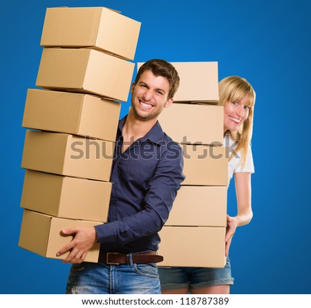Young Couple Holding Cardboard Box On Blue Background - stock photo