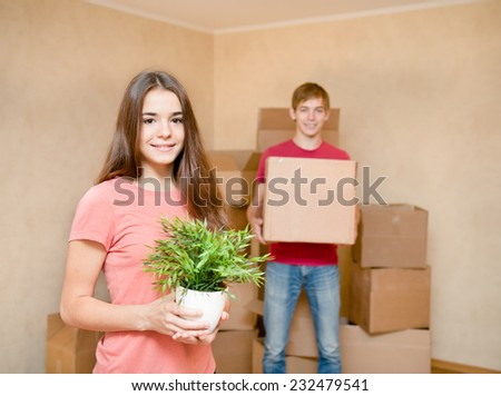 Young couple holding cardboard boxes for moving into a new house - stock photo