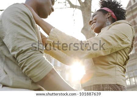 Young couple holding each other in the city with the sunset sun filtering through their bodies. - stock photo