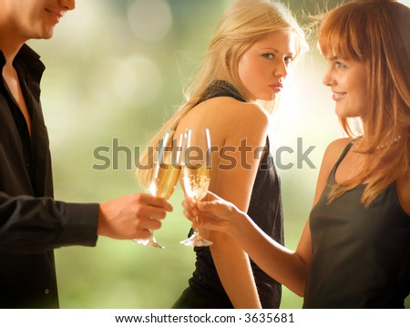Young couple holding glasses with champagne and woman looking at them, outdoors, focus on woman with blond hair - stock photo