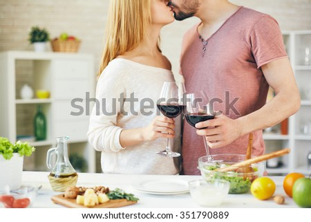 Young couple holding glasses with red wine and kissing in the kitchen - stock photo